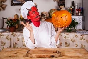 Mann im Teufels-Koch-Kostum, der einen geschnitzen Kürbis in der linken Hand hält