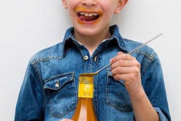Junge isst Kürbis Ketschup mit einem Löffel aus der Flasche